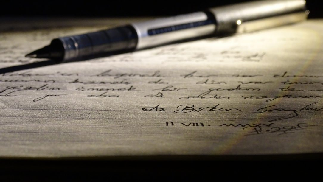 A pen laying on a piece of paper with script writing on it.