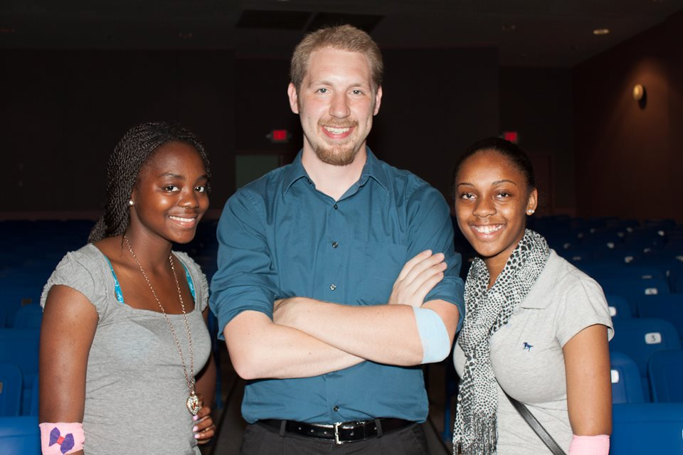 A man is standing in between two young women, and each of them has a bandage on their arm from donating at a blood drive.