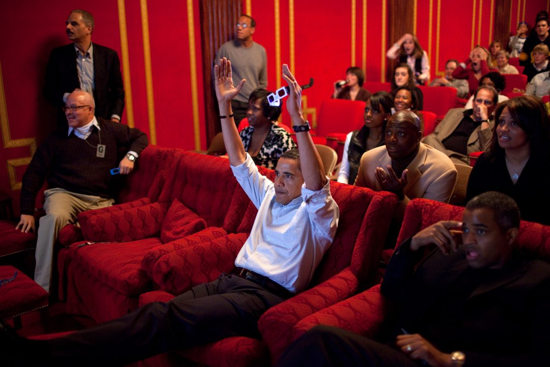 Barack Obama in a theater watching the 2009 superbowl, signaling a touchdown.