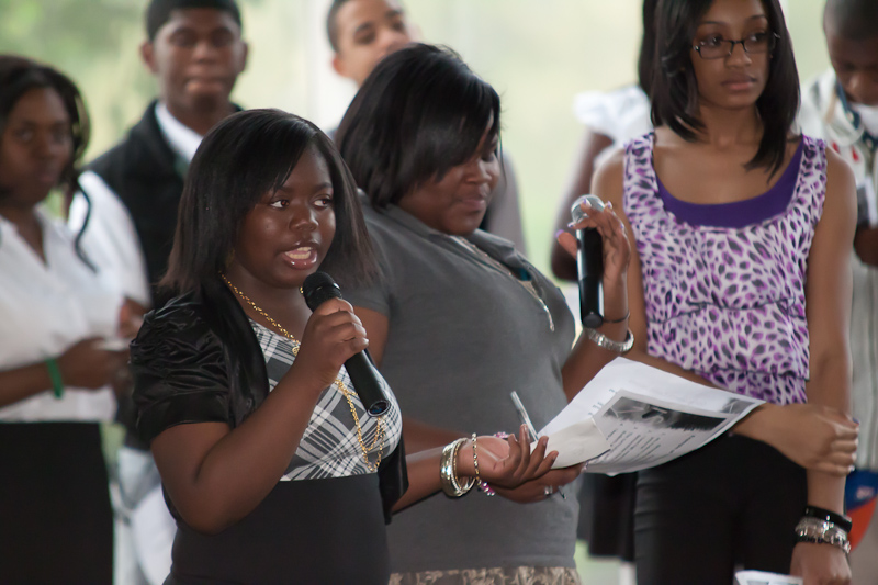 A student is speaking into a microphone sharing her research, while two other students stand in the background waiting for their turn to speak.