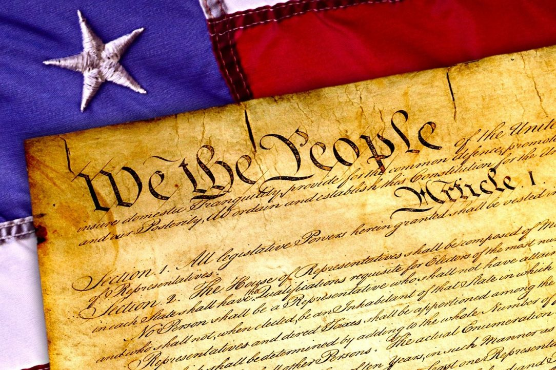 A civics oriented picture of the United States Constitution laid over an American flag.