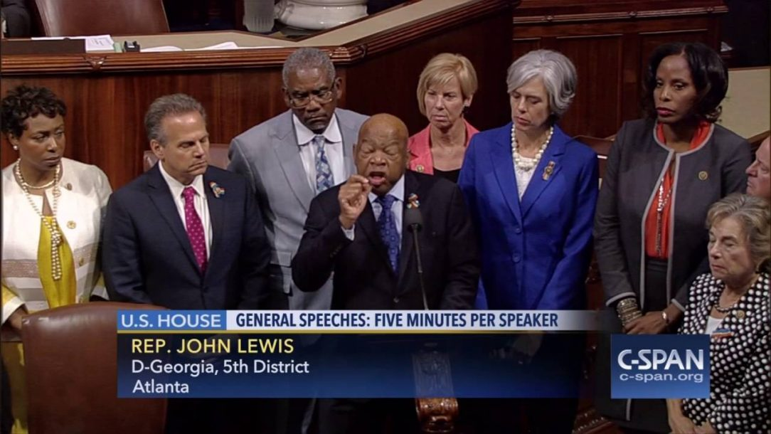 Rep. John Lewis giving a floor speech on the House floor with other Representatives standing behind him.