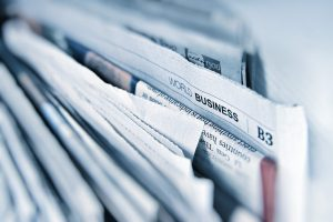 Stack of newspapers with the business section emphasized