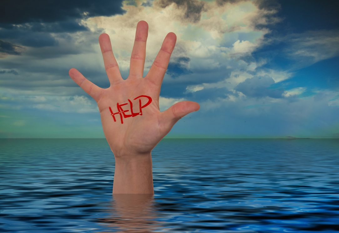 "A hand sticking out of the ocean with ""help"" written on it."
