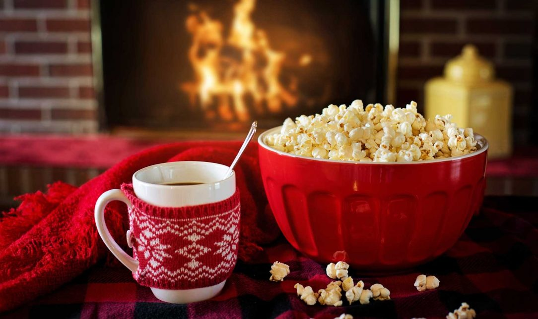 Popcorn and Hot Chocolate on a table in front of a Fireplace
