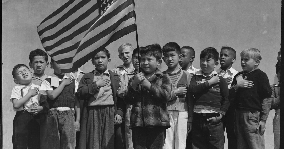Students holding a flag and pledging allegiance