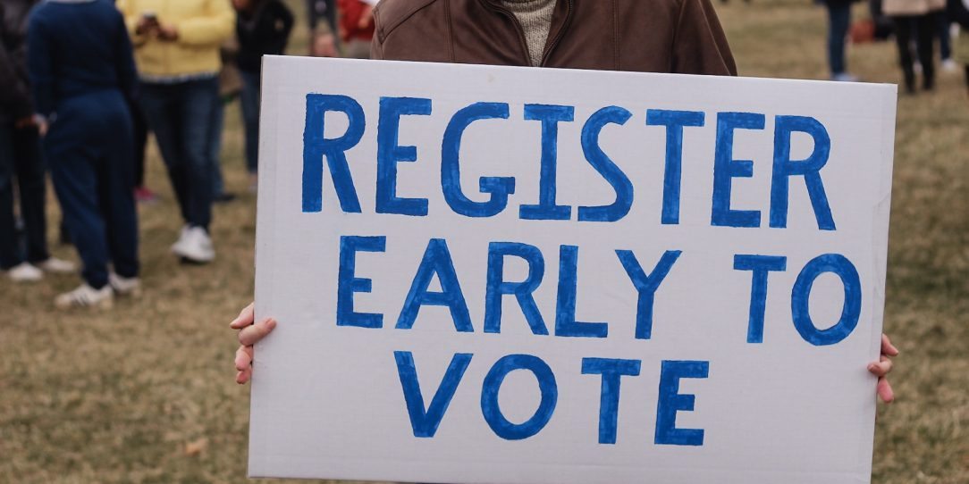 "Man holding a sign saying, ""Register Early to Vote"""