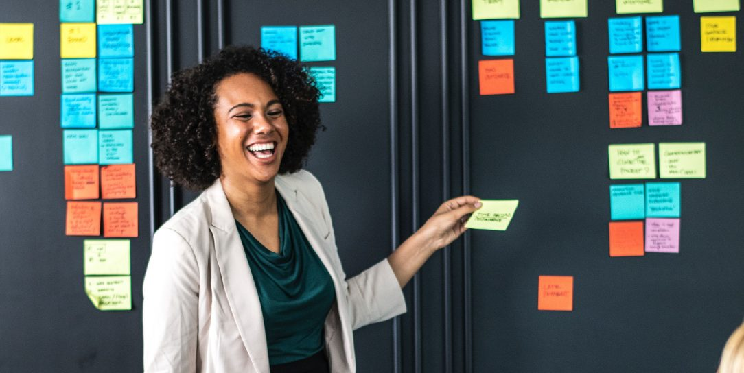 Two women have a discussion about sticky notes, organized around essential questions and themes.