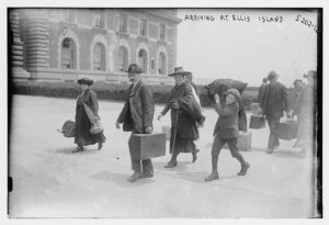 Group of immigrants walking on Ellis Island, carrying their suitcases. In black and white.