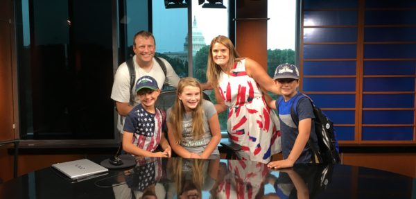 C-SPAN Teacher Fellow Sunshine, with her family, posing for a picture in one of C-SPAN's studios.