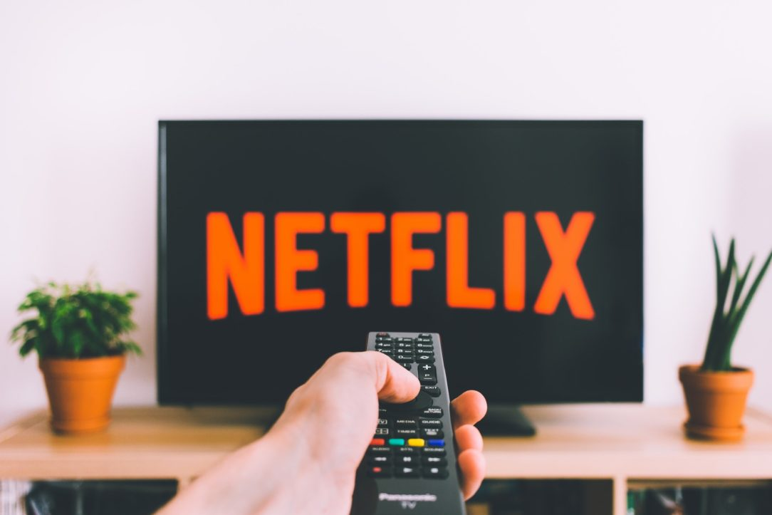 "A hand holding a remote in front of a TV with the ""Netflix"" logo."