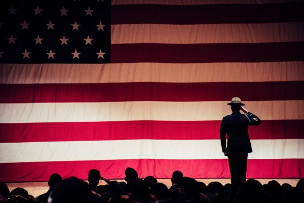 The silhouette of a soldier salutes a large American flag as other silhouetted soldiers look on.