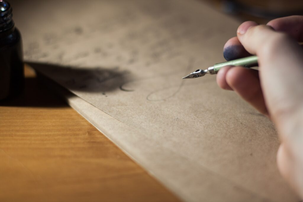 A person writing a letter with an old fashioned pen. Writing a letter about a current and controversial issue is a great method for teaching civics.