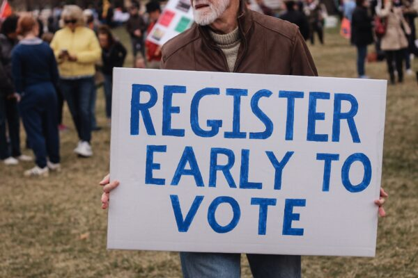"Man holding a sign that says, ""Register Early to Vote."" Teach voting rights."