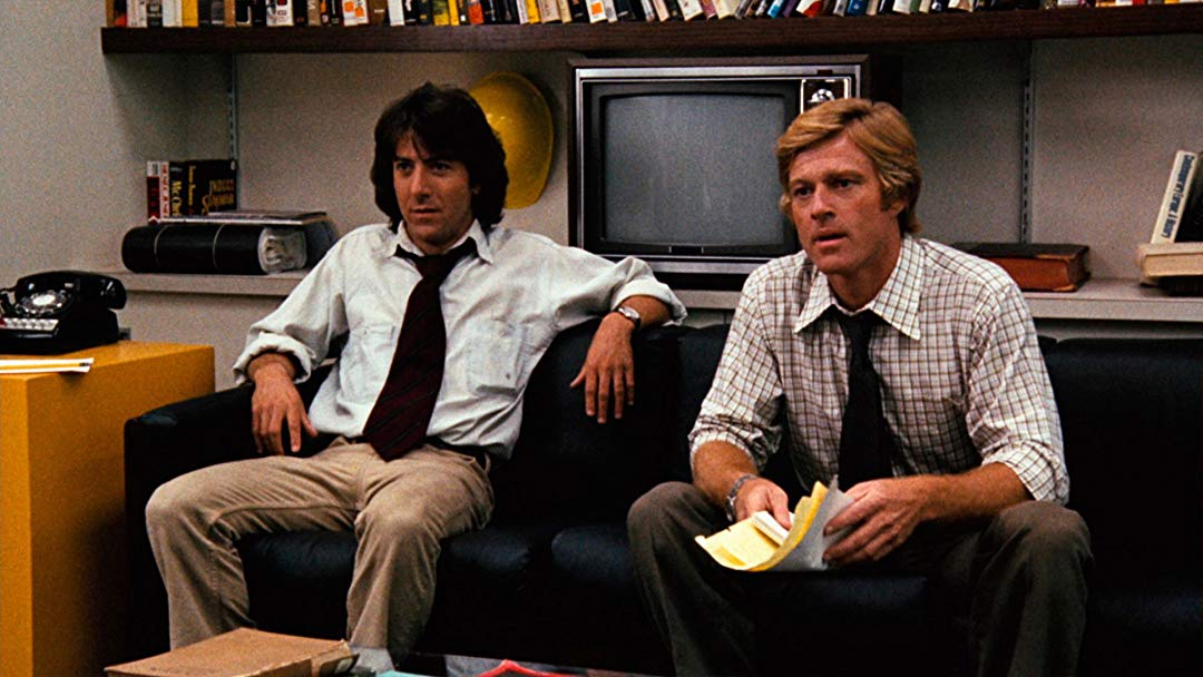 Actors Dustin Hoffman and Robert Redford sitting on a couch, portraying the journalists Bob Woodward and Carl Bernstein in All the President's Men.