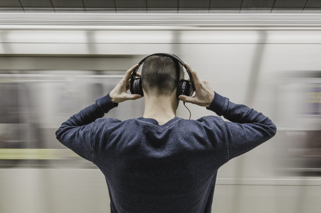 Man wearing headphones, watching a train go by. Slow down and listen to an audiobook about civics.
